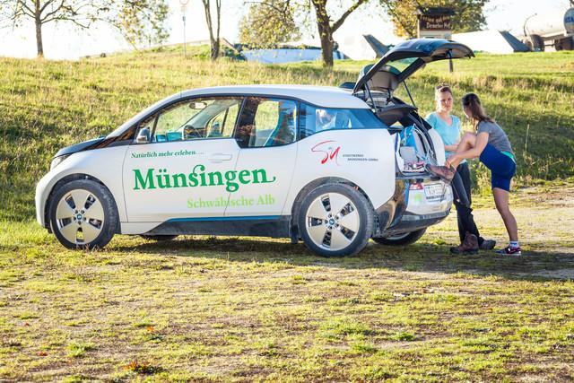 Zwei Wanderer*innen stehen an einem Auto mit der Aufschrift Münsingen Schwäbische Alb. Der Kofferraum ist geöffnet und eine Person stützt darauf mit ihrem Fuß ab und bindet den Wanderstiefel. Sie unterhält sich mit der Person daneben.