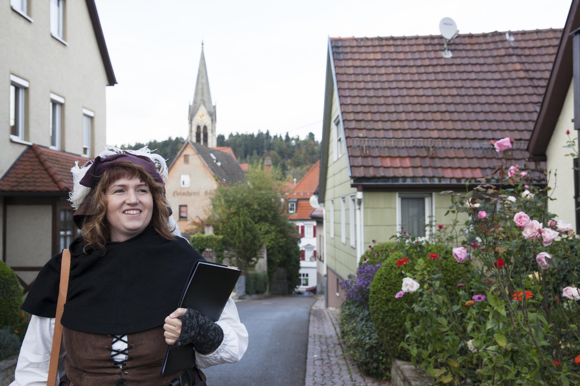 Eine Person in einem mittelalterlichem Kostüm schlendert grinsend durch die Straßen einer Stadt. Im Hintergrund ist der Kirchturm.