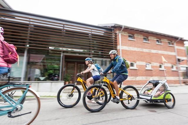 Zwei Erwachsene fahren mit E-Bikes am Biosphärenzentrum Schwäbische Alb vorbei. Eine*r zieht einen Kinderanhänger in dem zwei Kinder sitzen.