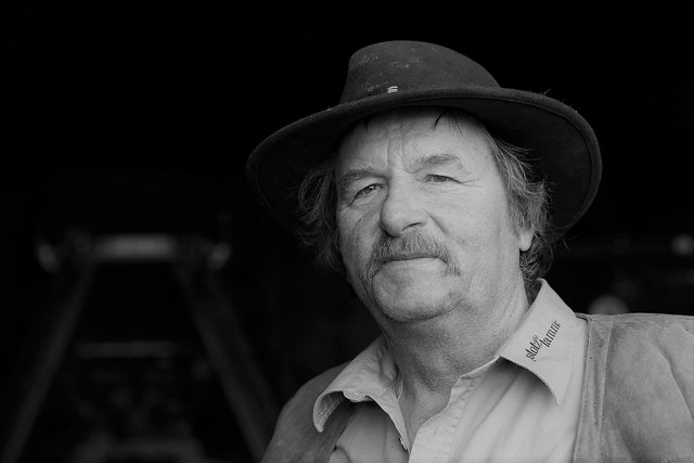 Ein schwarz-weiß Bild einer Person mit Hut, Hemd, einer Weste und einem Schnurrbart blickt entspannt in die Kamera. Auf seinem Hemdkragen steht Stotz Lamm.