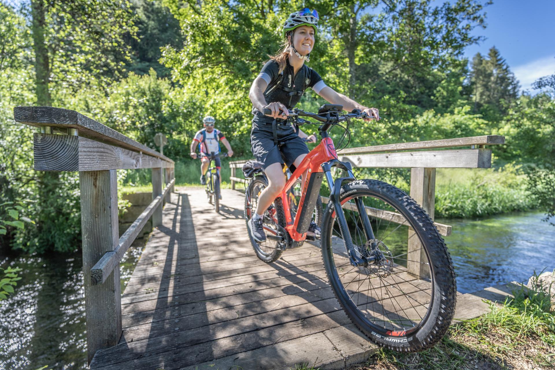 Zwei Radfahrer*innen fahren mit E-Bikes über eine Holzbrücke, die über einen Fluss führt. Im Hintergrund ist Wald. Die Sonne scheint und es ist warm.