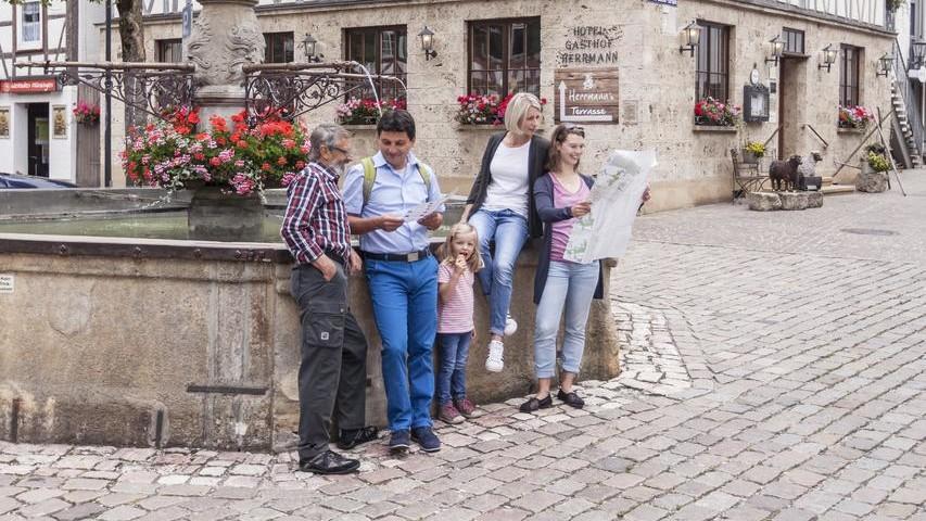 Vier Erwachsene und ein Kind stehen bzw. sitzen an einem Brunnen, der mit Blumen und einem Wappen verziert ist. Sie schauen in eine Karte. Im Hintergrund ist ein Fachwerkhaus mit einem Nasenschild.