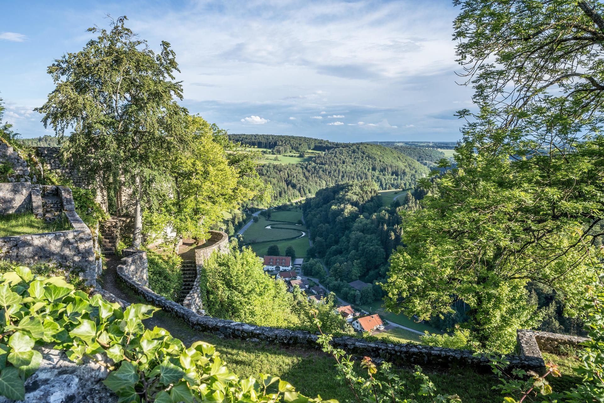 Der Ausblick von einer Burg über ein weites Tal, durch das sich ein Fluss schlängelt und in dem ein kleines Dorf liegt. Ringsherum sind bewaldete Hügel. Die Landschaft erstrahlt in saftigem grün und der Himmel ist leicht bewölkt.