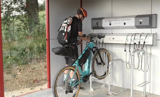 Ein*e Radfahrer*in steht in an einem Fahrrad, das mit dem Vorderrad in einem Radständer klemmt und sucht ein Kabel.