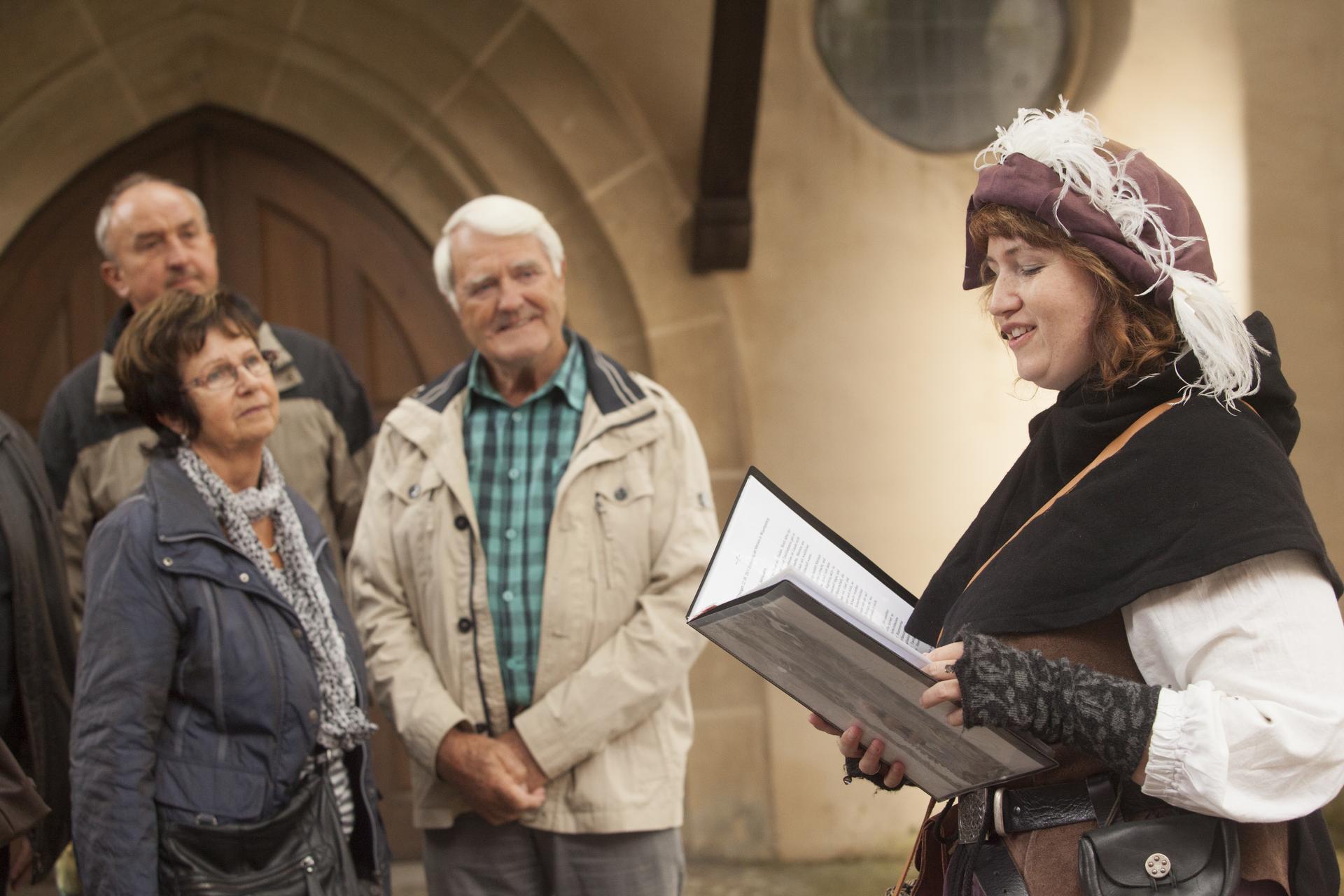 Eine Person in einem mittelalterlichen Kostüm liest lächelnd in einem Buch. Neben ihr stehen verschwommen Personen, die ihr zuhören.