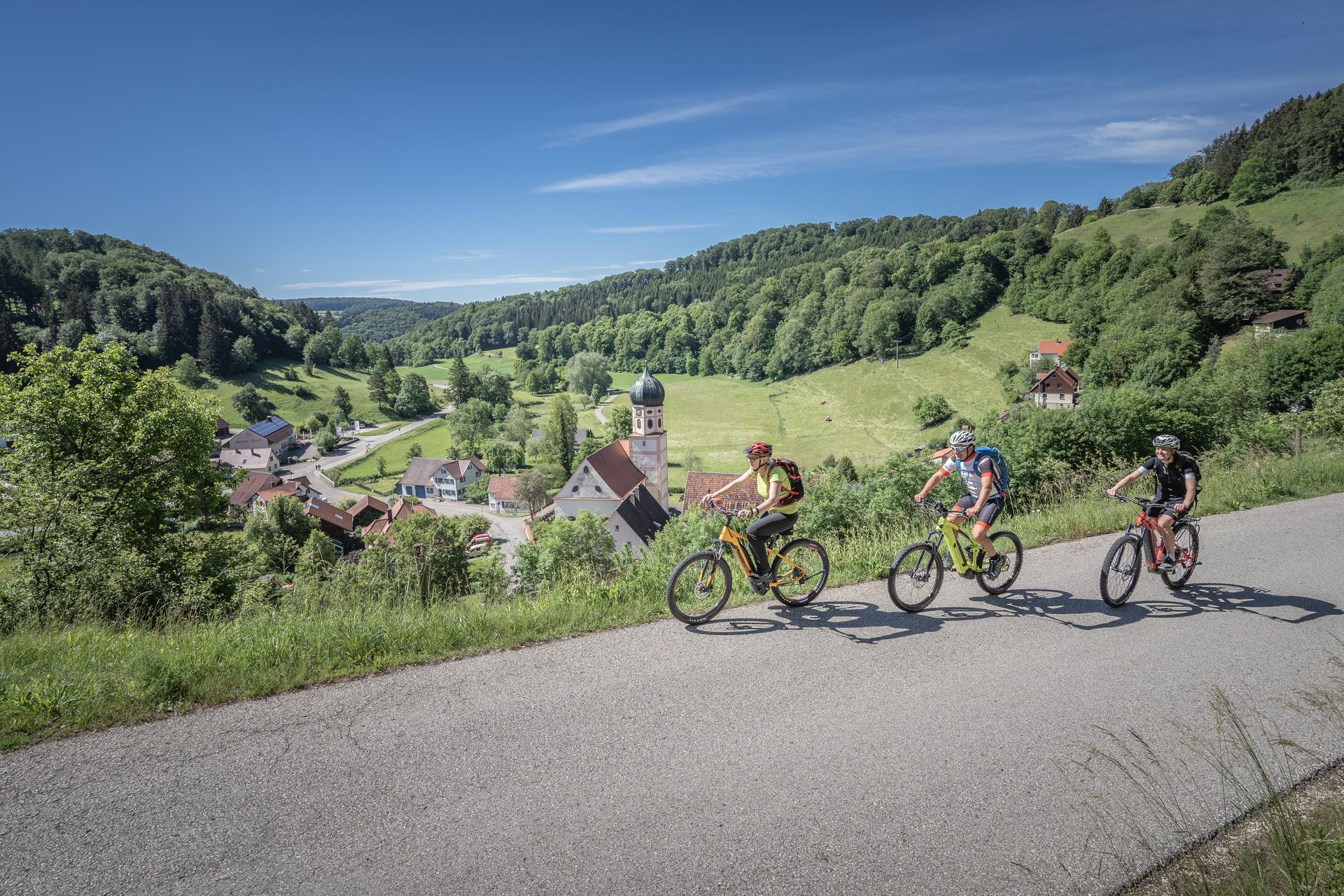 Drei Radfahrer*innen fahren mit E-Bikes einen Teerweg leicht bergauf. Im Hintergrund ist ein weites Tal, in dem ein Dorf liegt. Es ist sonnig.