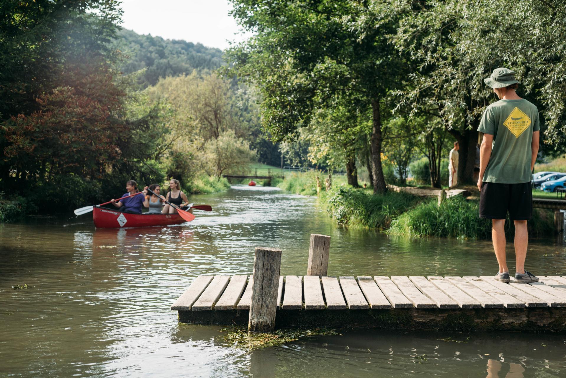 Auf einem Steg an einem Fluss steht eine Person mit Hut und blickt zu einem Kanu mit drei Personen, die gerade vorbei paddeln. Am Ufer sind Bäume und Pflanzen.