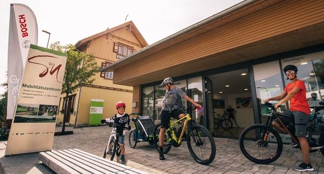 Zwei Erwachsene und ein Kind stehe in kurzer Radkleidung mit ihren Fahrrädern vor einem Gebäude. Die beiden Erwachsenen haben E-Bikes und einer einen Kinderfahrradanhänger. Vor dem Gebäude steht ein Schild mit der Aufschrift Mobilitätszentrum und eine Beach Flag von Bosch.