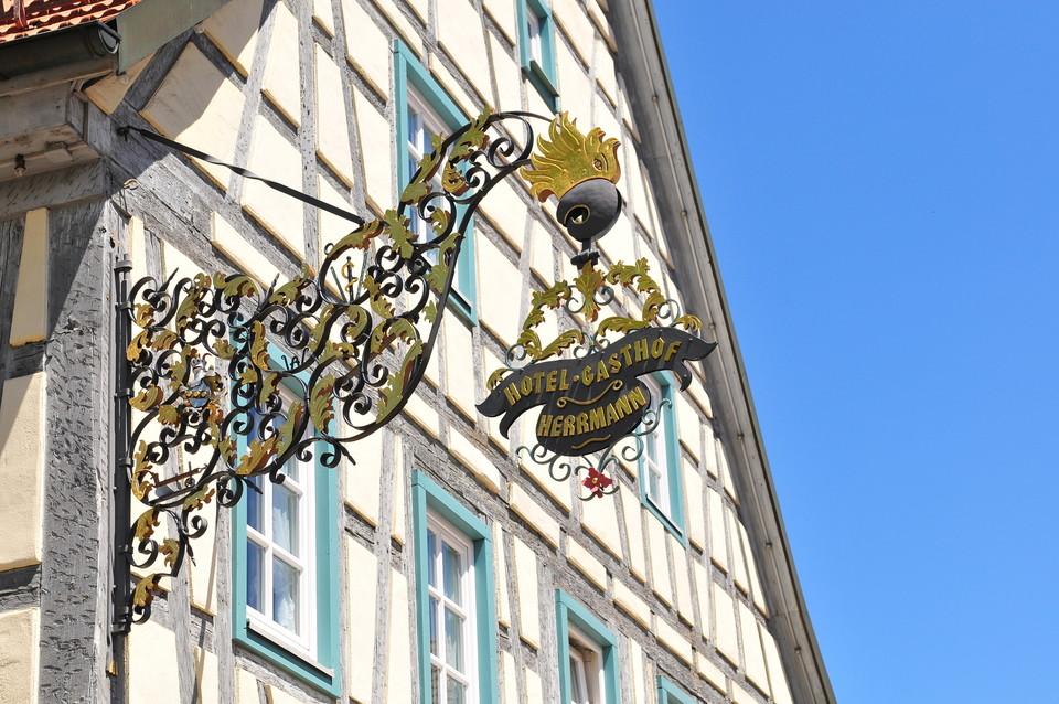 Ein Nasenschild an einem Fachwerkhaus mit der Aufschrift Hotel Gasthof Herrmann in gold-schwarz.