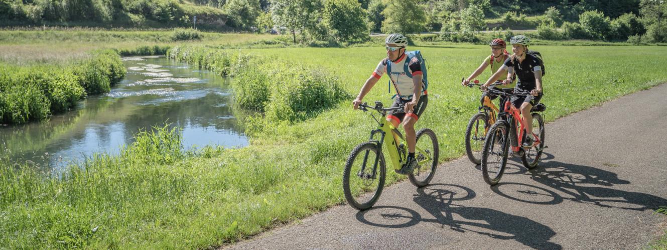 Drei Biker fahren am Fluss in Münsingen.