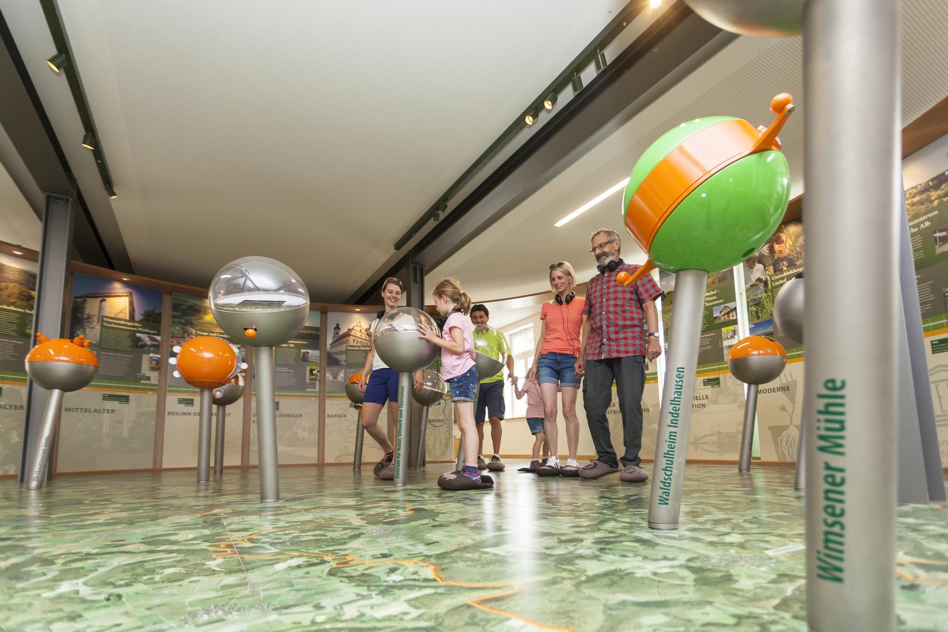 Mehrere Personen laufen über eine große Landkarte auf dem Boden. Überall stehen verschiedene Kugeln auf Säulen. Ringsherum sind Erklärtafeln.
