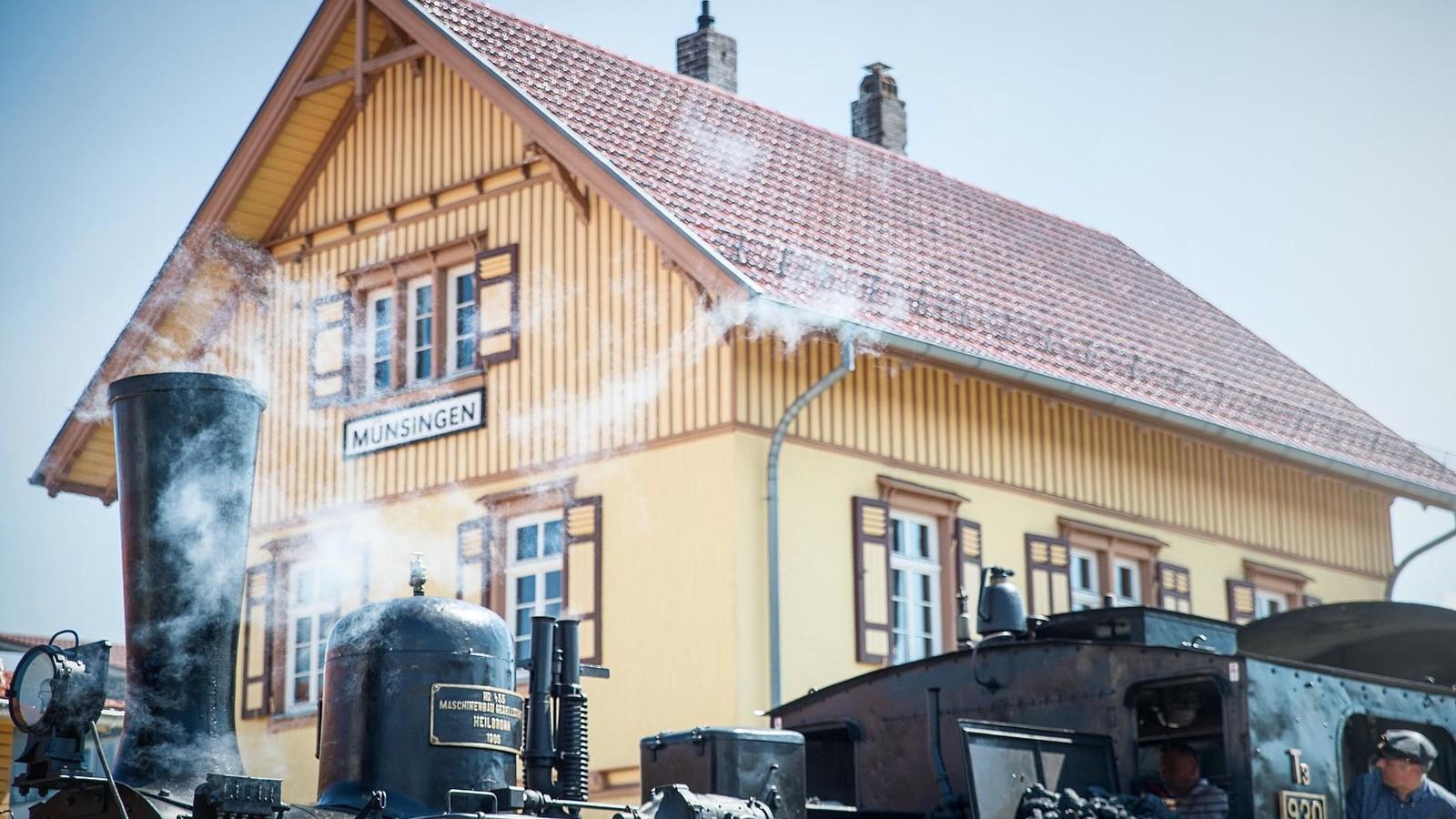 Eine historische Dampflok steht vor einem gelben historischen Gebäude mit dem Schild Münsingen. Aus dem Kamin kommt Dampf. Zwei Personen sind in der Lokführer-Kabine.