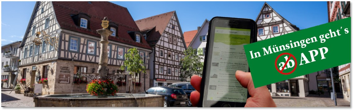 Der Münsinger Marktplatz mit dem Marktbrunnen im Sommer.  Von unten ragt eine Hand mit einem Handy ins Bild und daneben ein banner mit der Aufschrift In Münsingen geht´ s APP.