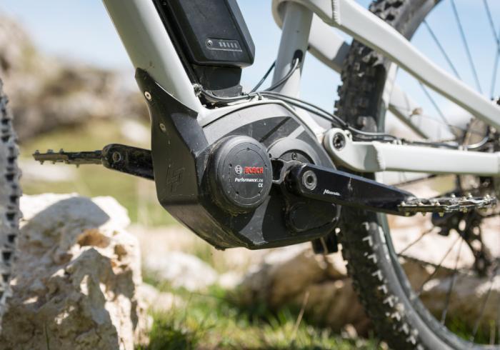 Eine Nahaufnahme eines e-Bike Bosch Motors. Der Rahmen des Fahrrads ist grau.
