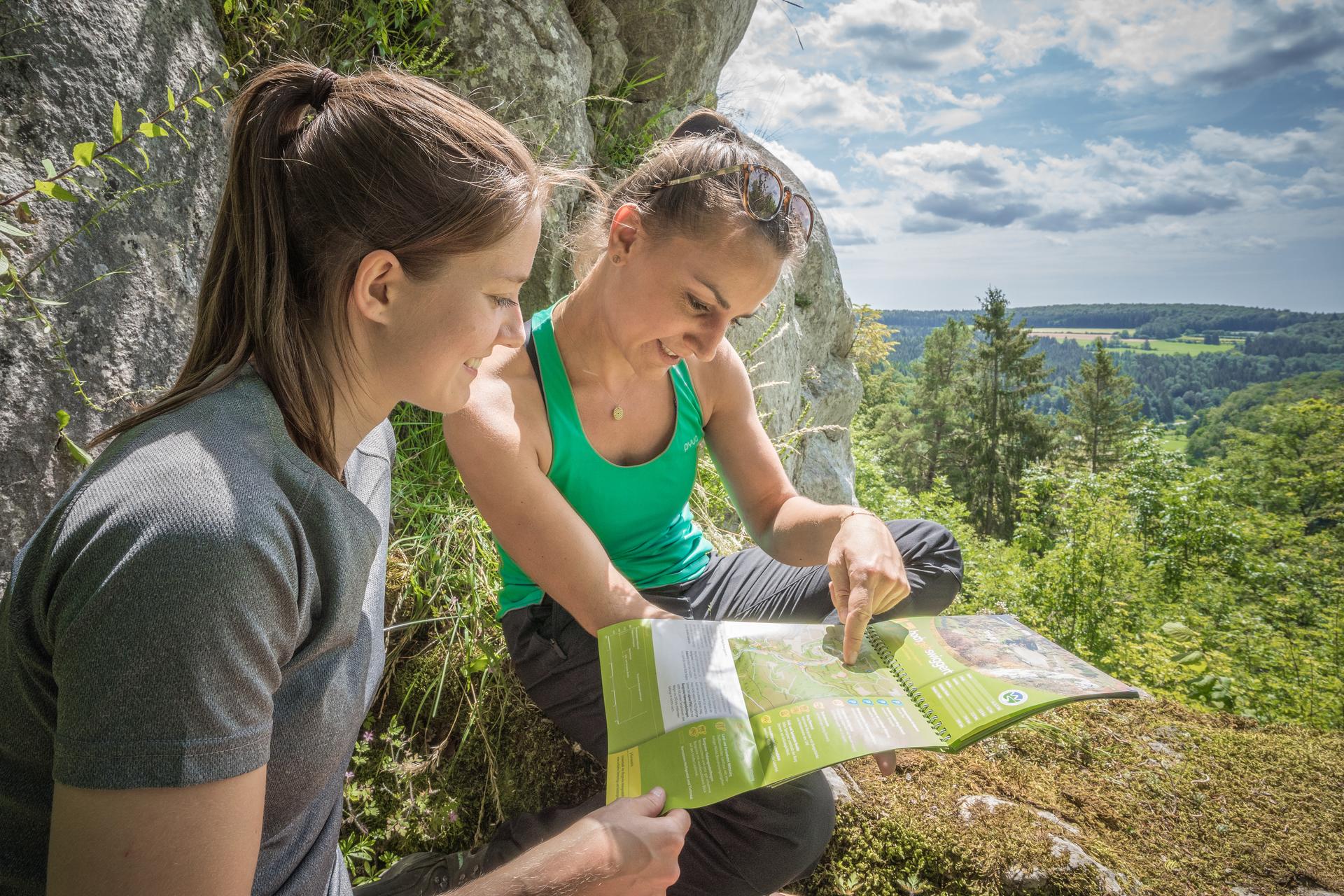 Zwei Personen sitzen an einem Fels auf einer Steinmauer und schauen in eine grüne Broschüre zum Aufklappen. Eine zeigt mit dem Finger darauf, beide lächeln. Im Hintergrund ist ein weiter Ausblick über den Wald und Felder. Der Himmel ist bewölkt, aber es ist sonnig und warm.