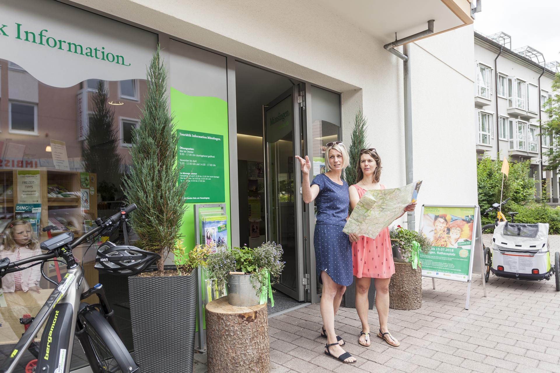 Zwei Personen kommen aus der Touristik Information Münsingen und halten eine Landkarte in der Hand. Sie Blicken in die Richtung, in die eine Person zeigt. Beide tragen kurze Somerkleider. Links und rechts stehen Fahrräder.