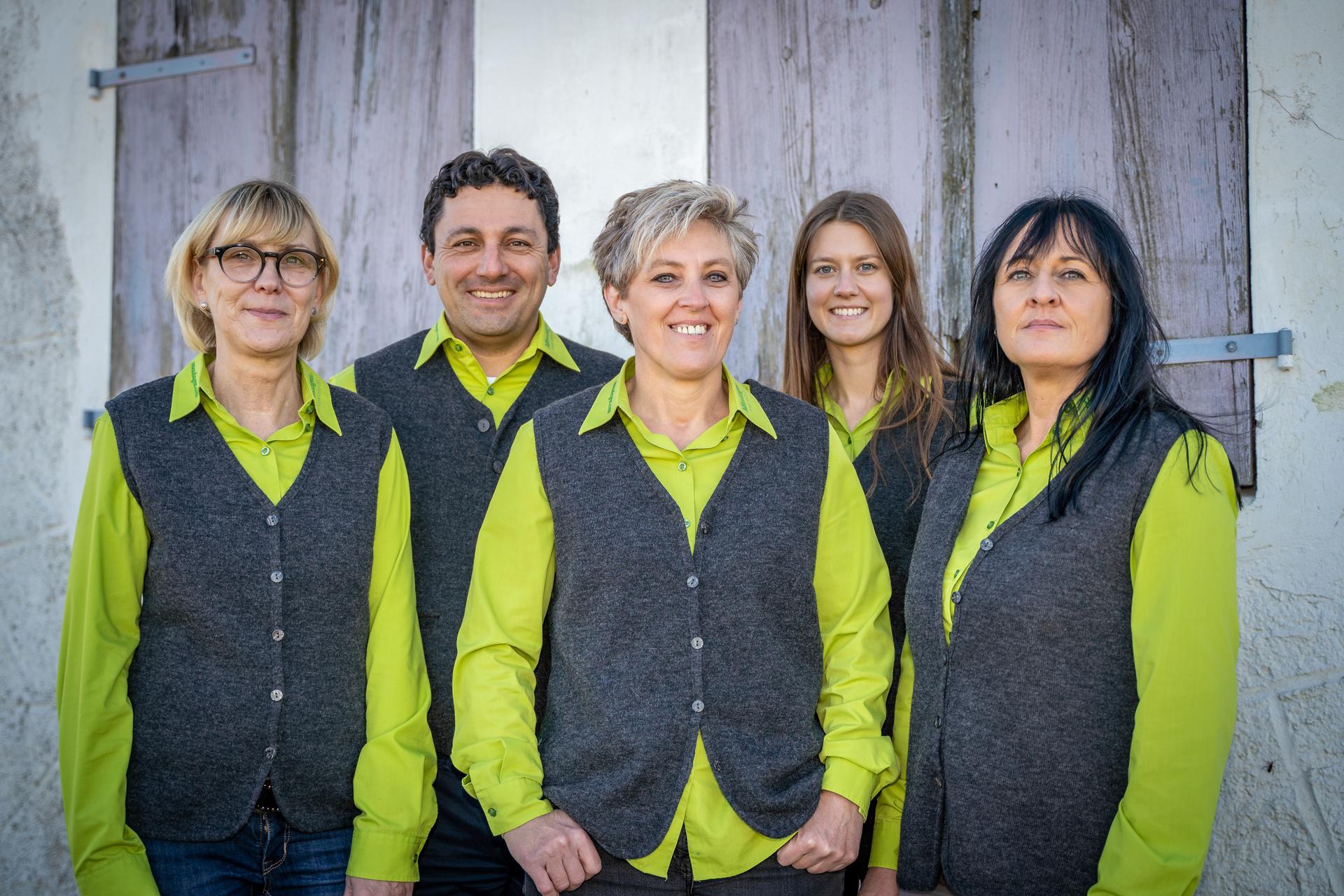 Drei Personen stehen vorne, zwei dahinter auf Lücke. Alle lächeln in die Kamera und tragen eine grüne Bluse mit einer grauen Weste.