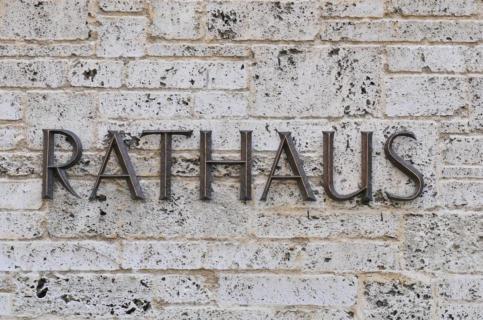 An einer Wand aus Stein sind große kupferfarbene Buchstaben mit dem Wort Rathaus.