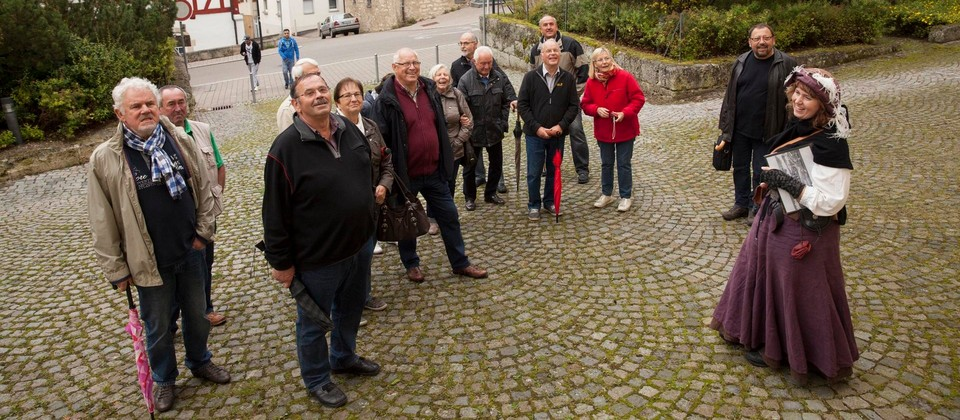 Eine Person in einem mittelalterlichen Kostüm steht vor einer Gruppe von Personen und lächelt. Die Gruppe blickt fasziniert nach oben. Sie stehen auf einem Platz, der von Gebäuden und Bäumen umrandet ist.