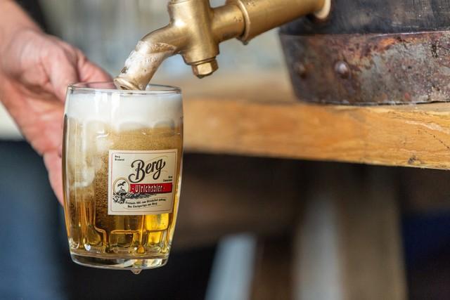 Ein Bierglas wird unter einen Zapfhahn gehalten und wird mit Bier befüllt. Auf dem Glas steht Berg Ulrichsbier.