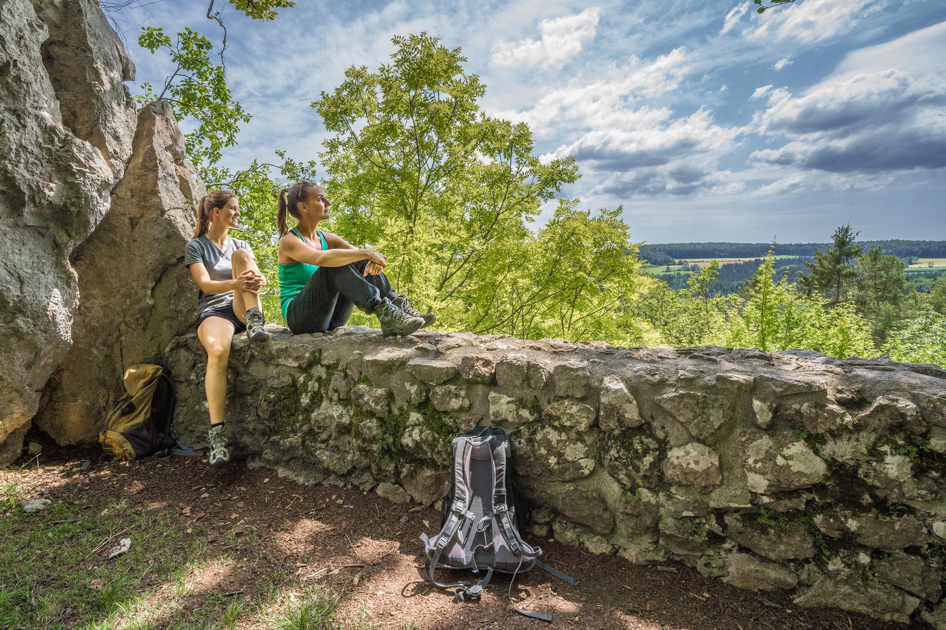 Zwei Wanderer*innen sitzen auf einer Mauer und blicken in die Ferne. Hinter ihnen ist eine Felswand. Vor ihnen ein Ausblick über einen Wald und eine Hochfläche. Der Himmel ist leicht bewölkt.