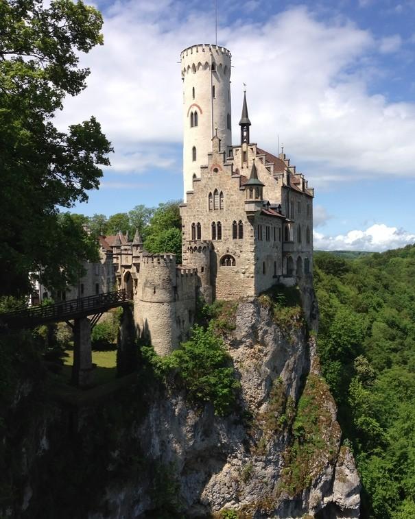 Ein Schloss mit einem weißen Turm auf einem Fels. Es kann nur über eine Brücke erreicht werden. Daneben ein Ausblick über eine Stadt in einem Tal. Die Hügel drumherum sind bewaldet. Der Himmel ist leicht bewölkt.