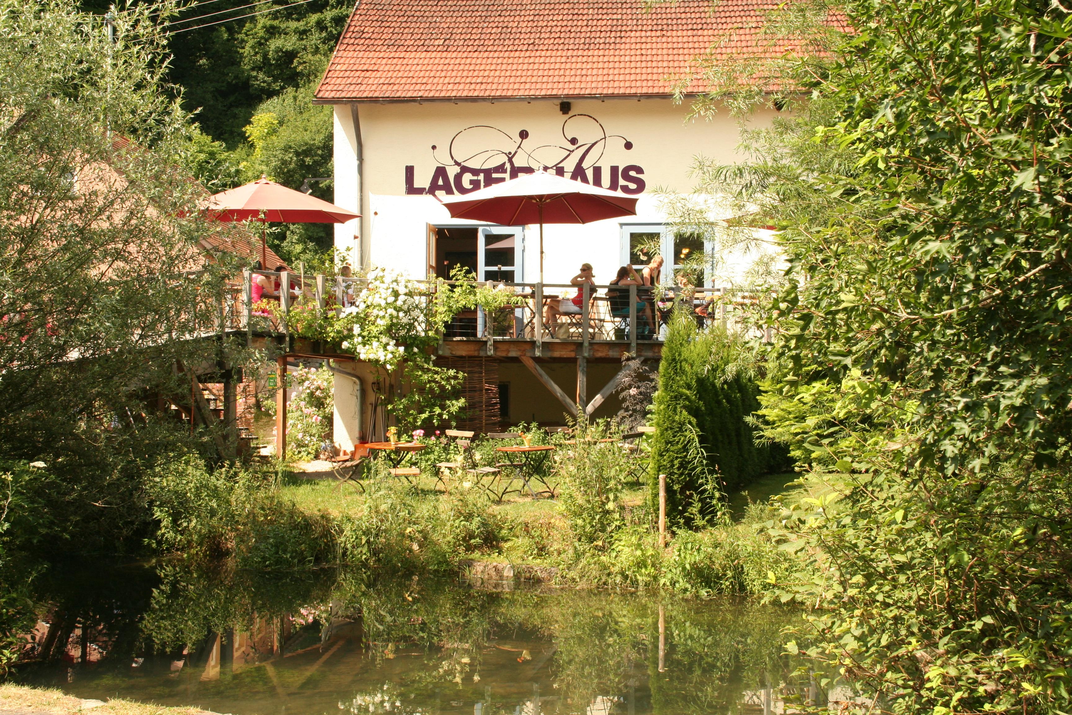Ein Gebäude mit der Aufschrift Lagerhaus, davor eine Terasse mit mehreren Tischen und Stühlen und Sonnenschirmen, davor eine kleine Wiese mit Tischen und Stühlen, die driekt an einem Fluss stehen. Es ist sonnig.