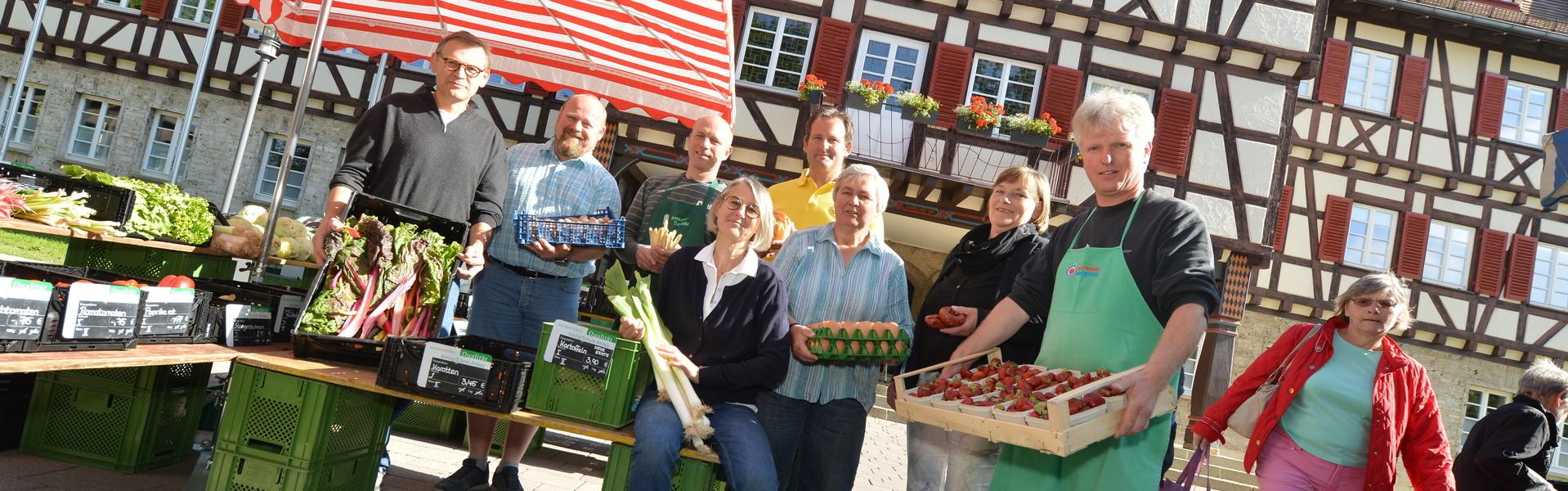 Eine Gruppe von Personen, die Lebensmittel wie Gemüse, Eier oder Brot in der Hand halten stehen unter einem rot-weißen Sonnenschirm und lächeln in die Kamera. Im Hintergrund ist ein Fachwerkhaus. Ringsherum sind Tische und weitere Kisten mit Lebensmittel.