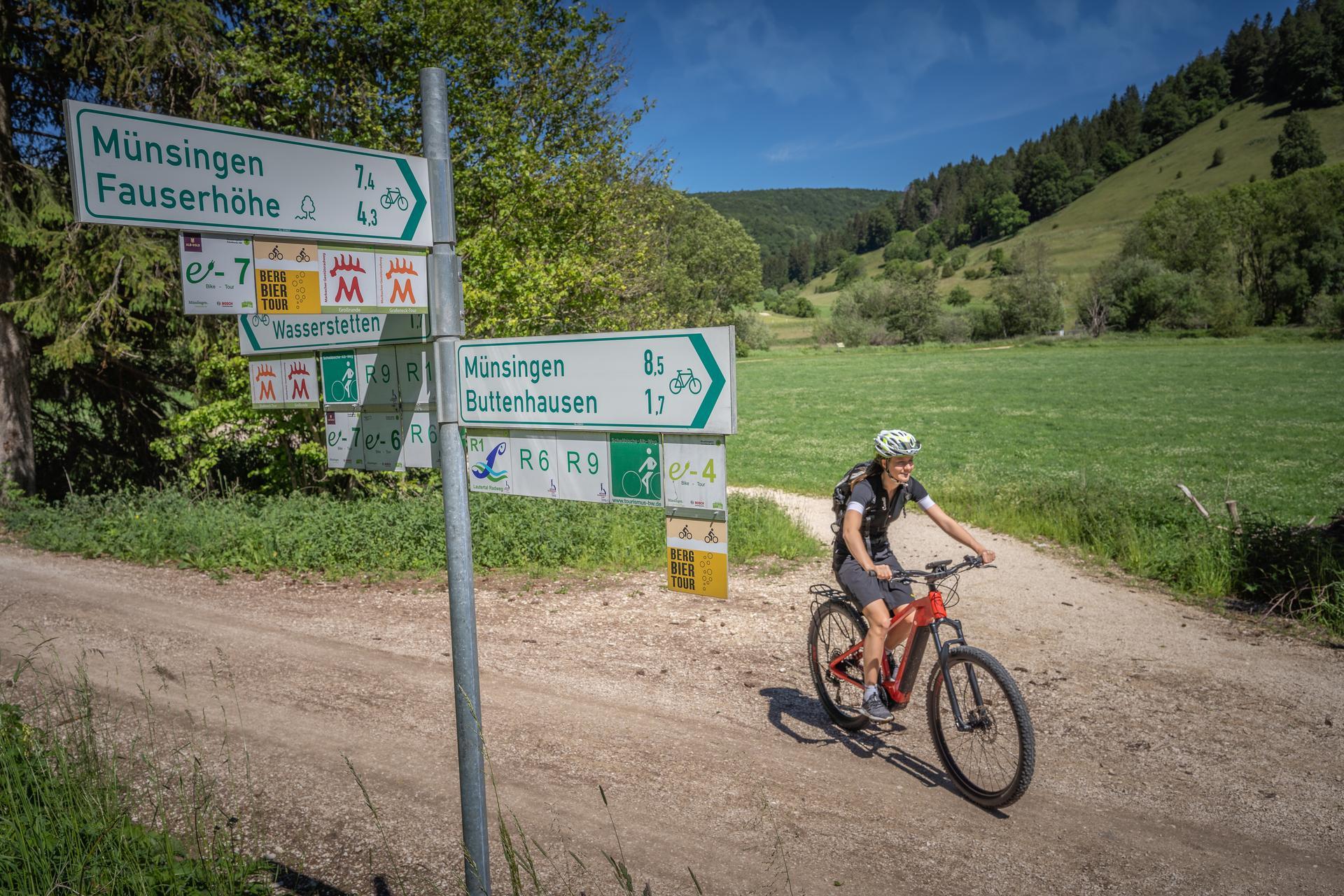 Ein*e Radfahrer*in fährt auf einem Schotterweg und biegt links an einer Gabelung ab. Im Vordergrund ist ein Schild/Radwegweiser.