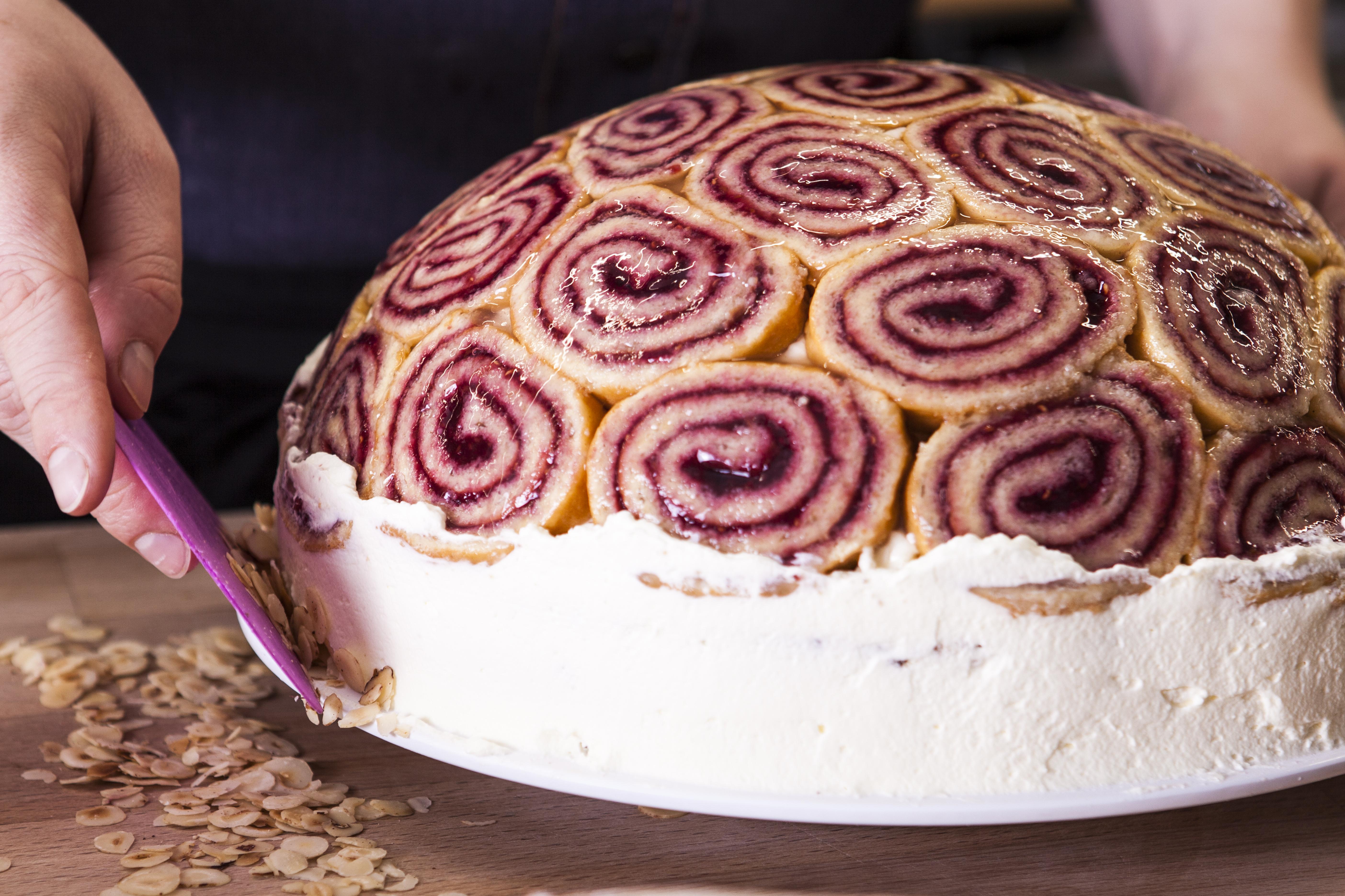 Eine halbrunde Torte wird von außen mit Sahne und Mandeln überzogen.