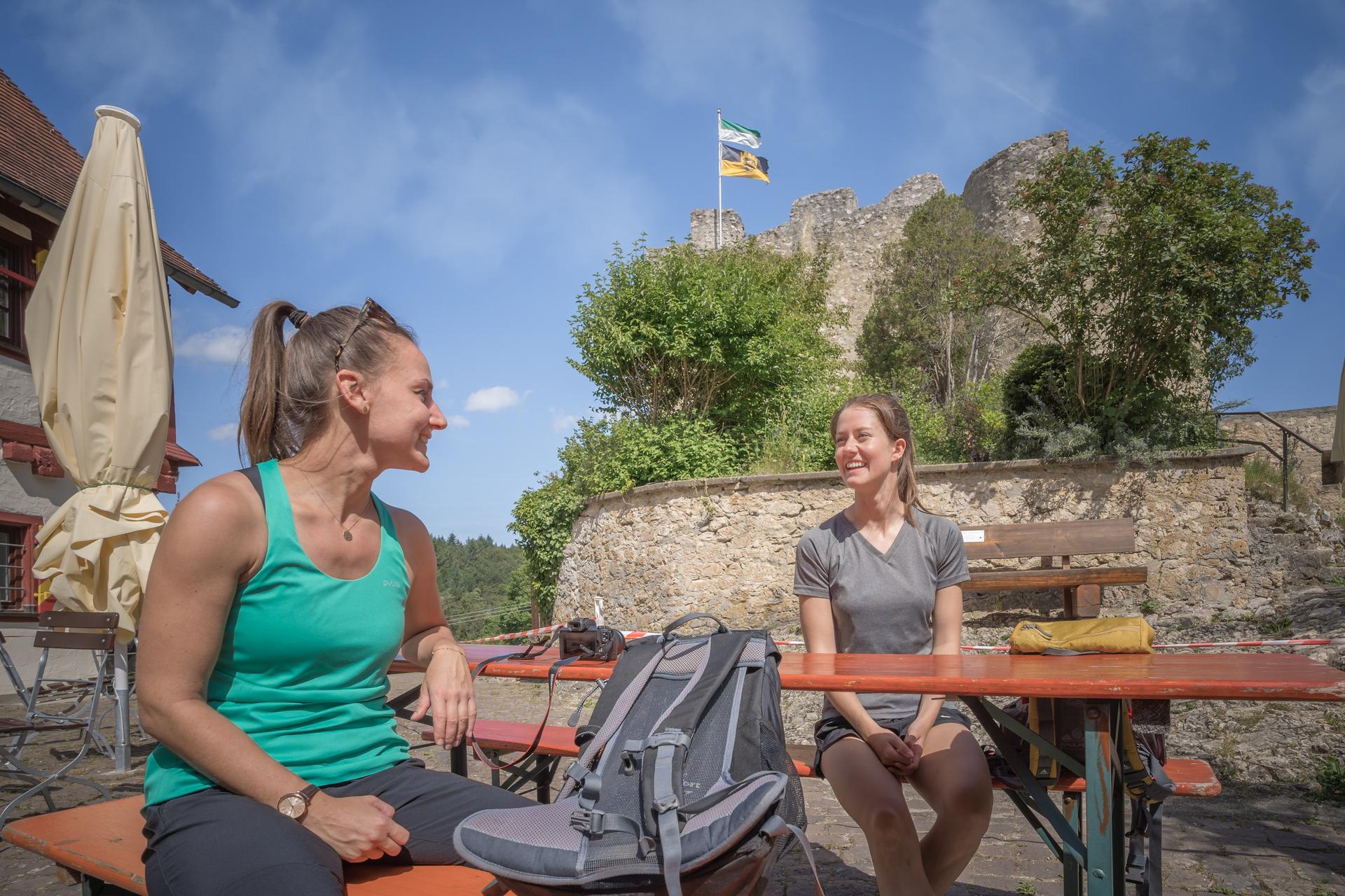 Zwei Wanderer*innen sitzen sich auf Bierbänken an einem Tisch gegenüber und lächeln sich an. Dahinter ist eine Burg mit zwei wehenden Flaggen. Der Himmel ist blau.