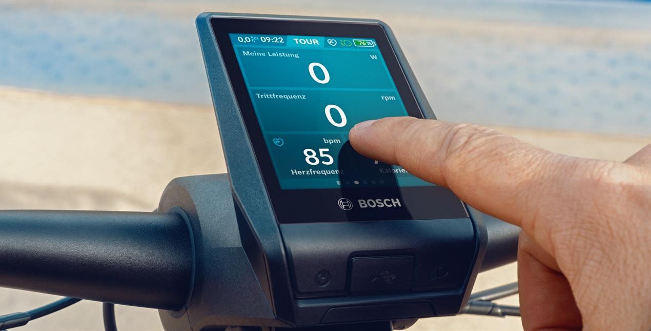 Eine Person zeigt mit einem Finger auf einen Fahrrad-Bordcomputer von Bosch.