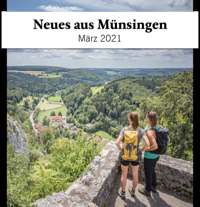 Zwei Wanderer*innen stehen auf einer Burg an einer Ecke einer Plattform. Sie stehen mit dem Rücken zum Fotograf und blicken in die gleiche Richtung ins Tal, durch das sich ein Fluss schlängelt und sich ein kleines Dorf befindet. Der Himmel ist leicht bewölkt und es ist warm. Darüber ist ein Banner mit der Aufschrift Neues aus Münsingen, März 2021.