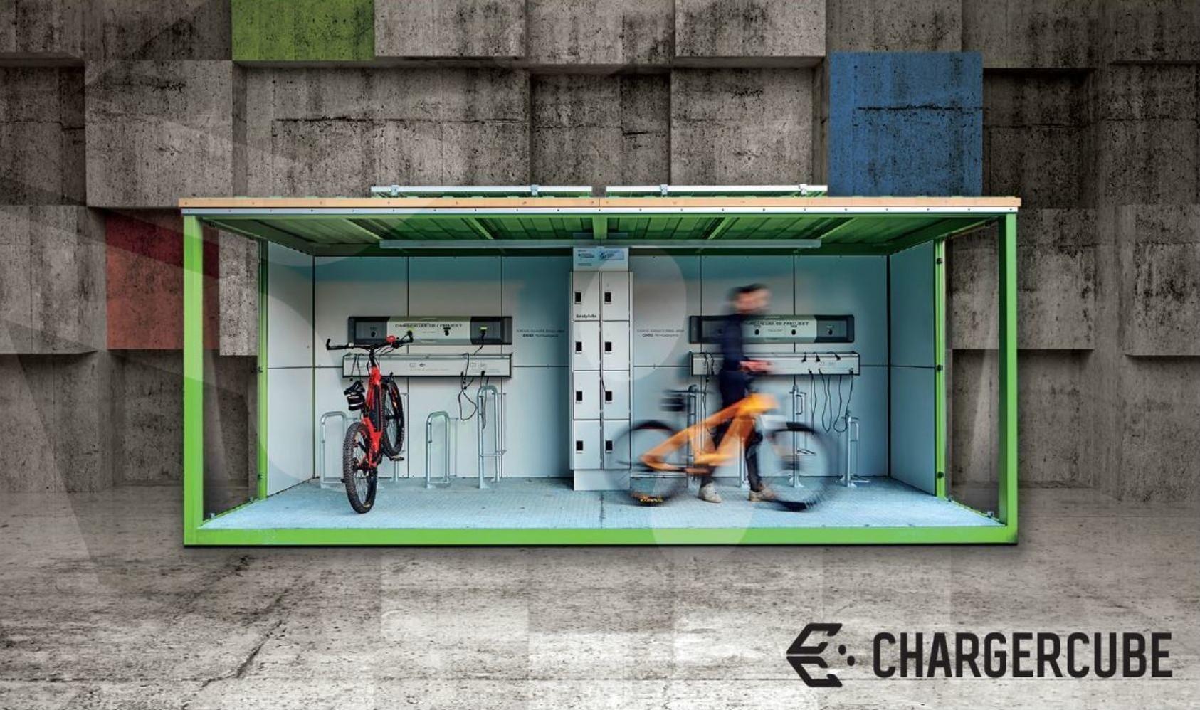Eine Postkarte über den ChargerCube mit der Überschrift Einfach Überall Stromtanken. Vor einem grauen Betonmauer steht ein grüner Ladewürfel in dem ein rotes Fahrrad steht. Eine Person ist verschwommen und schiebt ein Fahrrad mit sich.