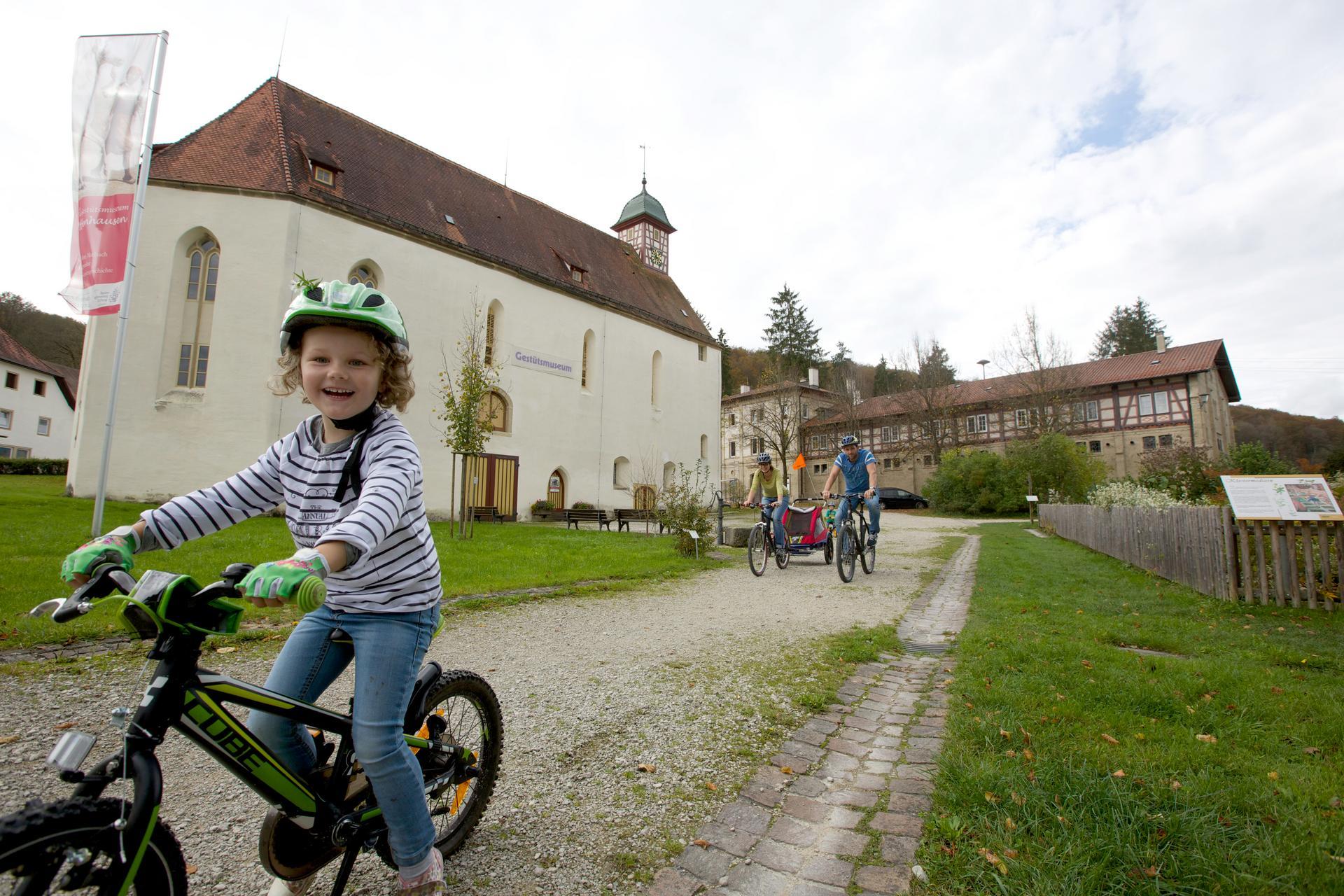 Ein Kind auf einem Fahrrad lacht in die Kamera. Hinter ihm kommen zwei Erwachsene ebenfalls mit dem Fahrrad und einem Kinderanhänger. Im Hintergrund sind große historische Gebäude und ein langer Gartenzaun.