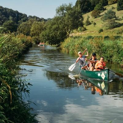 Drei Kanufahrer*innen paddeln durch einen schmalen Fluss. Das Ufer ist mit Pflanzen überwuchert, im Hintergrund kommen noch weitere Kanus. Die Sonne scheint und es ist warm.