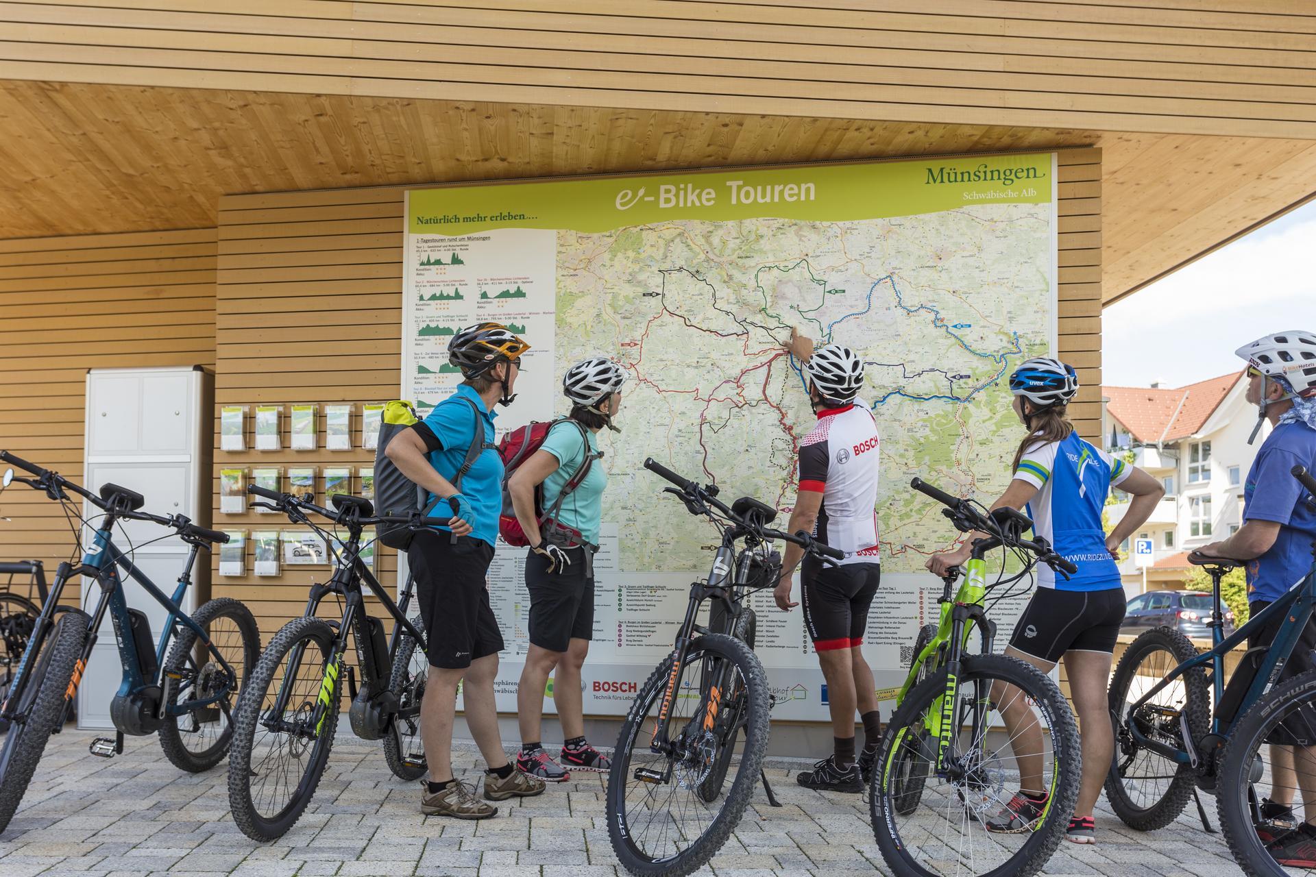 Fünf Radfahrer*innen stehen vor einer großen Landkarte mit den e-Bike Touren von Münsingen. Die Person in der Mitte zeigt darauf, die anderen blicken interessiert auf die Karte. Alle haben ein e-Bike und sind sportlich kurz gekleidet.