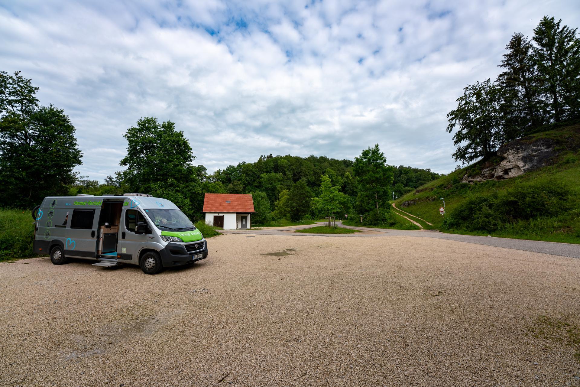 Auf einem großen Schotterparkplatz steht ein Campingbus. Dahinter ist ein kleines Häuschen. Drumherum sind Wiesen und Wälder in saftigem grün. Der Himmel ist leicht bewölkt.