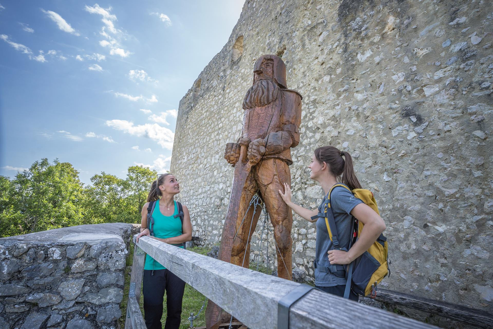 Zwei Wanderer*innen begutachten eine Ritterskulptur aus Holz. Hinter ihnen ist eine hohe Mauer. Die Sonne scheint und es ist warm.