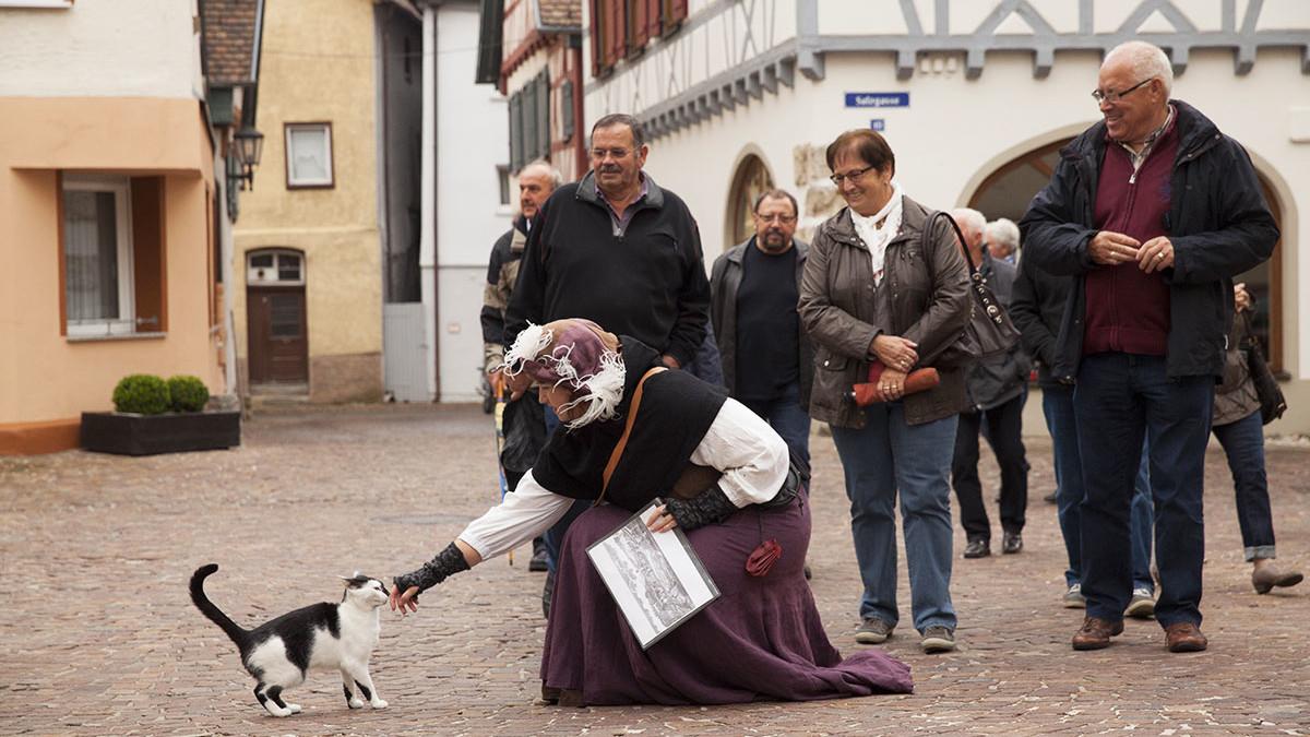 """Das """"Marktweib Marga"""" streichelt eine Katze bei der historische Stadtführung in Münsingen."""