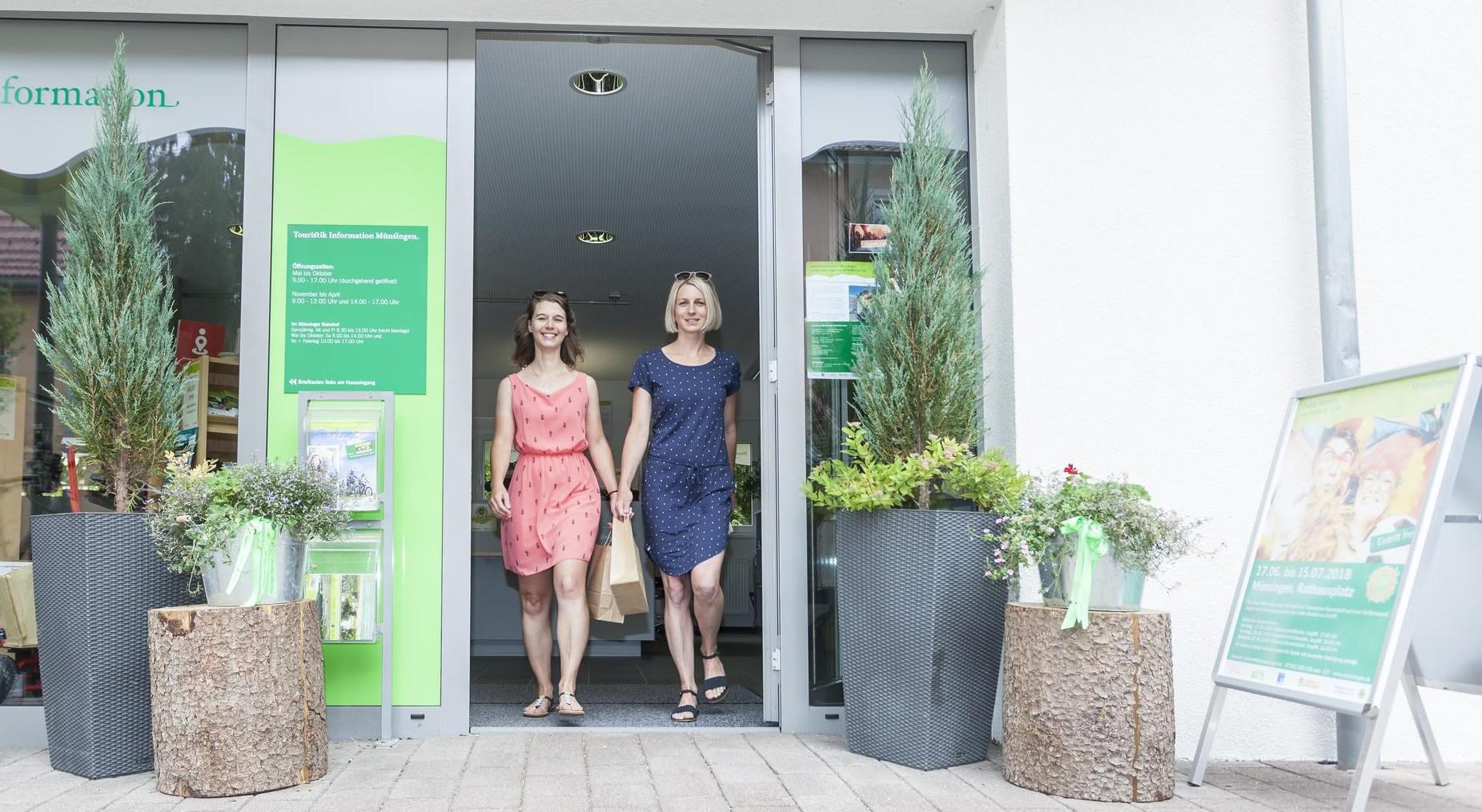 Zwei Personen laufen aus einem Laden mit Tüten in der Hand und lächelln in die Kamera. Links und rechts vom Eingang stehen dekorative Pflanzen.