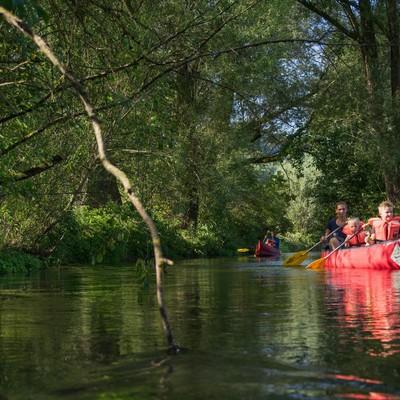 Zwei Kinder und eine Erwachsene sitzen mit Schwimmwesten in einem roten Kanu und halten Paddel in der Hand. Sie fahren auf einem schmalen Fluss, dessen Ufer links und rcehts mit Pflannzen überwuchert ist. Im Hintergrund kommt ein weiteres besetztes Kanu.