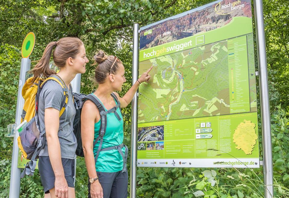 Zwei Wanderer*innen stehen vor einem Wanderschild mit Karte. Das Schild zeigt den Wanderweg hochgehswiggert der hochgehberge. Eine Person zeigt darauf.