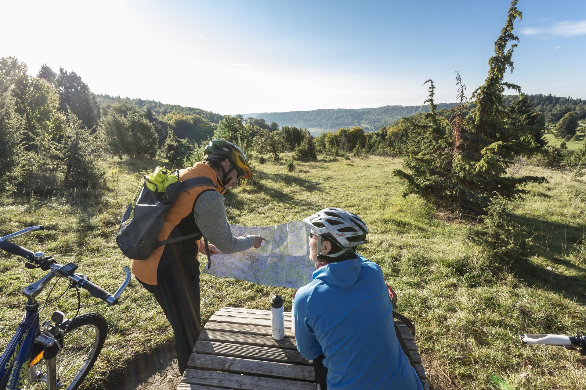 Zwei Radfahrer*innen rasten an einer Holzbank und werfen einen Blick in die Landkarte. Eine zeigt darauf. Neben ihnen ein Fahrrad. Vor ihnen der weite Blick über Tannenwälder und vereinzelte Wacholderheiden auf der Wiese. Die Sonne scheint.