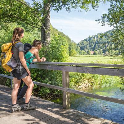 Zwei Wanderer*innen stehen auf einer kleinen Holzbrücke und blicken auf den Fluss. Im Hintergrund sind vereinzelt Häuser zwischen einer Waldfläche.
