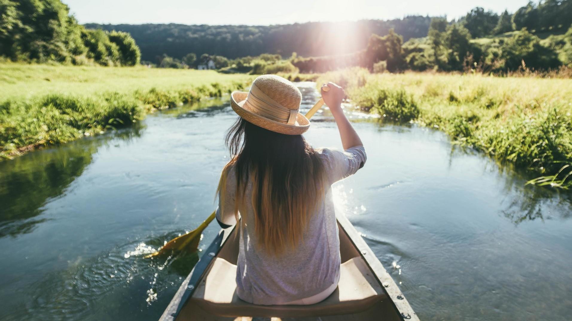 Eine Person sitzt vorne in einem Kanu und paddelt ruhig durch das Wasser. Sie trägt einen Sonnenhut. Links und rechts ist das dicht bewucherte Ufer. Die Sonne strahlt.