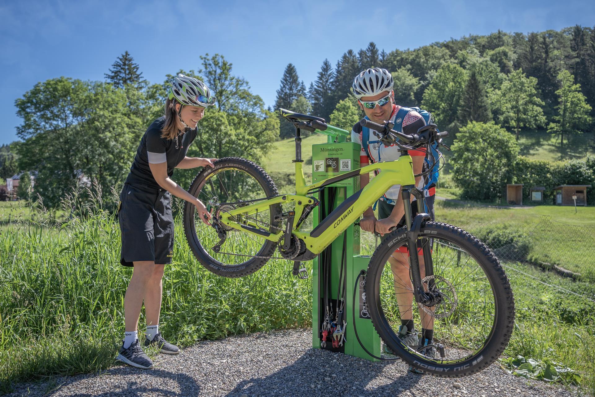 Zwei Radfahrer*innen stehen an einer Fahrradreparaturstation und hantieren an einem E-Bike, das auf dem Bikeständer hängt. Eine*r repariert die Schaltung, eine*r pumpt die Reifen auf. Es ist sonnig und warm.