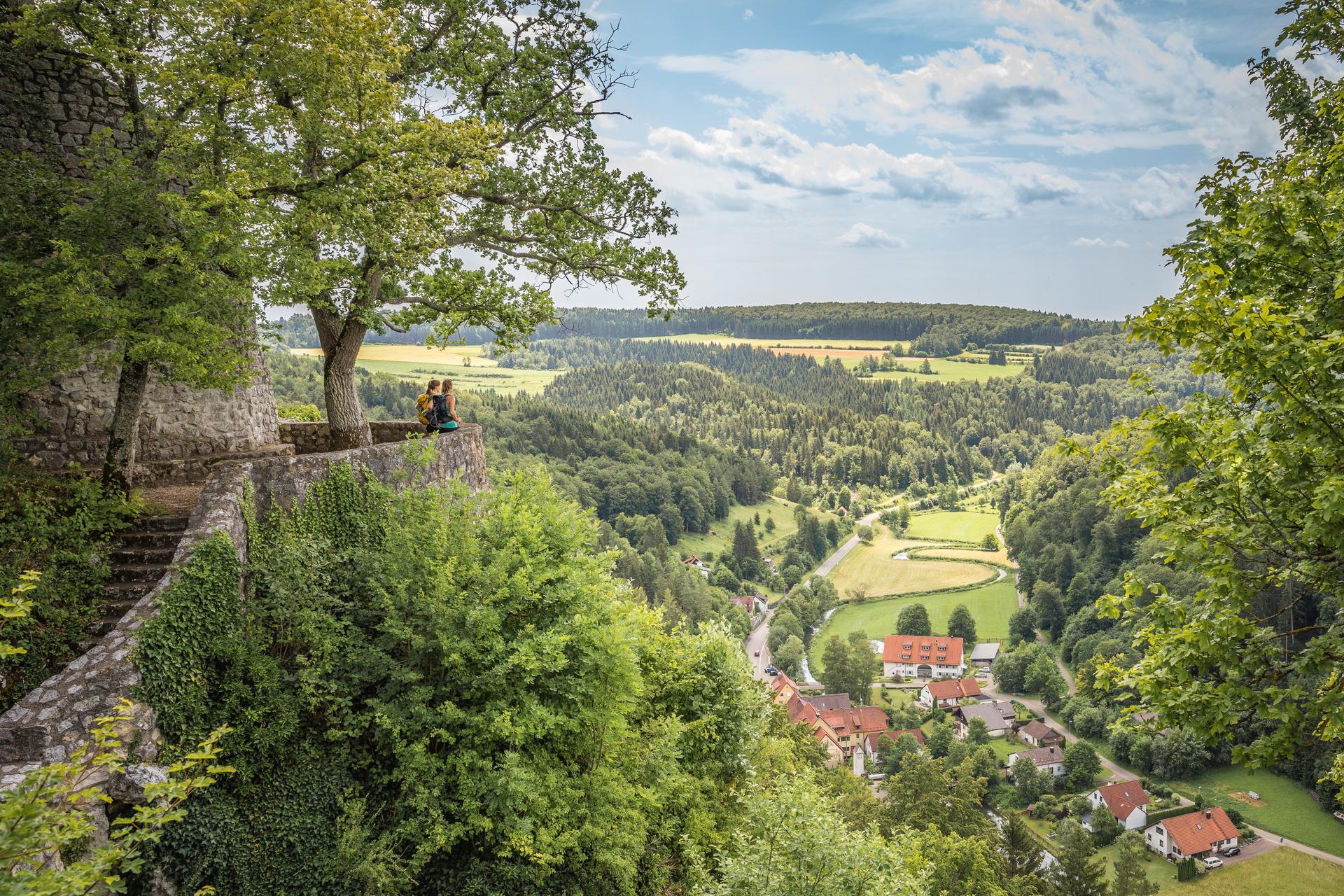 Zwei Wanderer*innen stehen auf einer Plattform an einer Burg. Sie blicken ins Tal durch das sich ein Fluss schlängelt und ein kleines Dorf liegt. Rundherum ist Wald. Es ist sonnig und bewölkt.