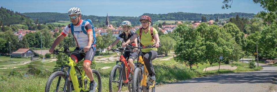 Drei E-Bike-Fahrer fahren eine Tour bei Münsingen.
